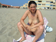 Mature aged women sunbathing topless..