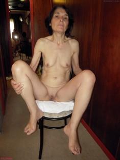 Skinny granny posing naked in the..